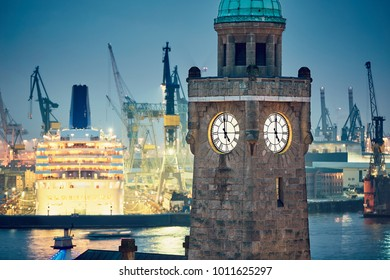 Industrial skyline at the night. Historical clock tower in harbor in Hamburg, Germany.