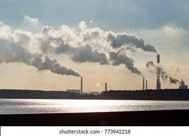 Industrial smoke from a plant on the shore of a lake