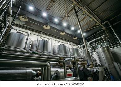 Industrial stainless steel fermentation vats in modern brewery