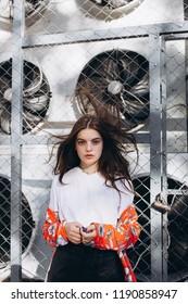 Industrial street modern fashion portrait of young beautiful caucasian girl posing outdoors. Beauty, fashion concept