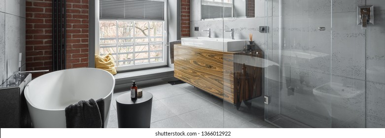 Industrial style bathroom with oval bathtub and walk in shower, panorama