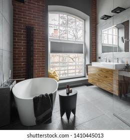 Industrial style bathroom with oval bathtub and big window
