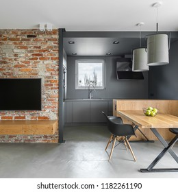 Industrial style home interior with brick wall, wooden table and open kitchen