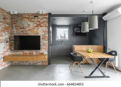 Industrial style home interior with kitchenette, tv, table, chairs and brick wall