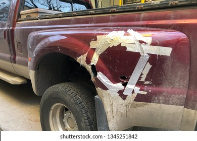 Industrial tape covers the holes and scratches of damaged truck rear fender. Left part of the damaged pickup truck body is covered with pieces of cellophane duct tape
