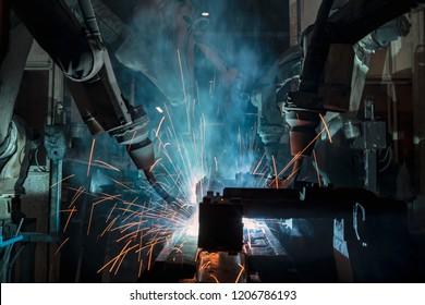 Industrial team robots are welding in factory