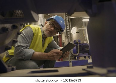 Industrial technician connected with tablet in recyling plant