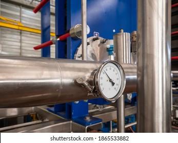 Industriethermometer auf einem Edelstahlrohr in einer Industriehalle. Plattenwärmetauscher auf dem Hintergrund