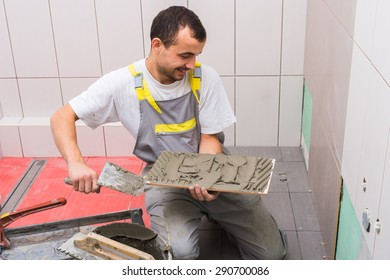 industrial tiler builder worker installing floor tile
