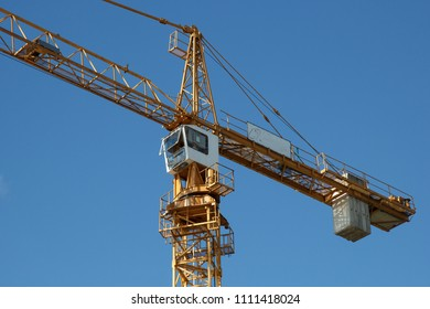 industrial tower crane cabin against blue sky