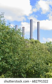 Industrial towers in green forest area with trees. Nature versus man.