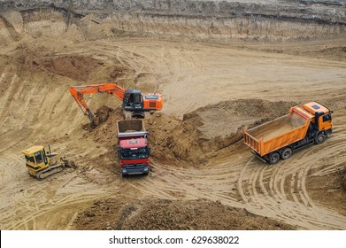 Industrial truck loader excavator moving earth and unloading into a dumper truck and bulldozer is moving ground