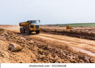 Industrial truck tipper bin moves earth on new industrial property earthworks development plateau in countrysidse