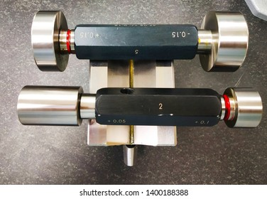 Industrial used plain plug gauges rest on V- block. APlug Gauge(orgo/no-go) refers to an inspection tool used to check a workpiece against its allowedtolerances
