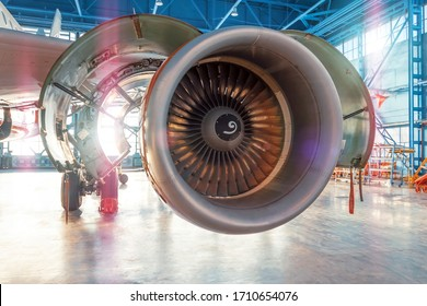 Industrial view of the airplane engine with an open hood for repair in aviation hangar, with bright light outside the gate