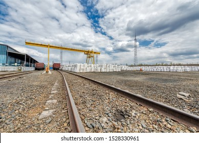 Industrial warehouse. A railroad has been brought to the warehouse. Big bags with bulk substance are stored at the warehouse.