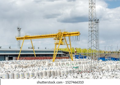 Industrial warehouse for the storage of bulk technological materials. A large number of white plastic bags with mineral powder. Big yellow gantry crane.