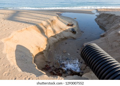 Industrial wastewater, the pipeline discharges liquid industrial waste into the sea on a city beach. Dirty sewage flows from a plastic sewer pipe onto the sand of a sea city beach