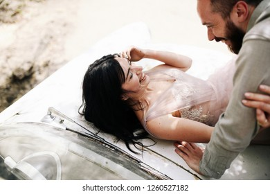 Industrial wedding concept. Charming groom and bride in rose pink dress look happy having a rest on the hood of an old car