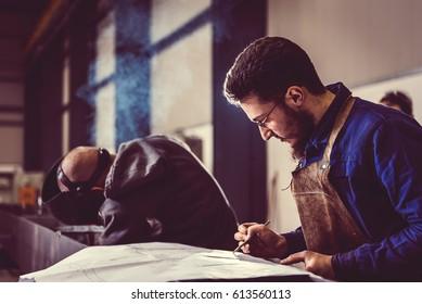 Industrial Welder checking blueprint in the background welder welding metal profiles