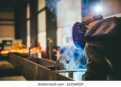 Industrial Welder With Torch and Protective Helmet in big hall welding metal profiles