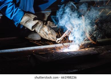 Industrial welder welding fabricated construction in factory, Welding process by Shielded Metal Arc Welding (SMAW) or Stick Welding.