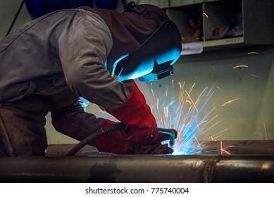 Industrial welder welding fabricated construction in factory Welding process by Shielded Metal Arc Welding (SMAW) or Stick Welding.