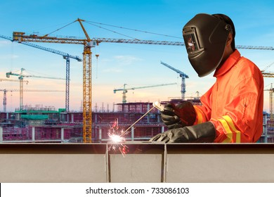 Industrial welder welding steel structure construction by metal arc welding or stick welding at building construction