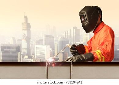 Industrial welder welding steel structure construction by metal arc welding at high building construction against urban scene.