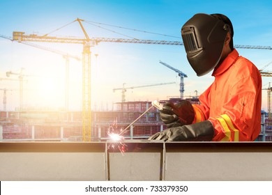 Industrial welder welding steel structure construction by metal arc welding or stick welding at building construction in sunrise