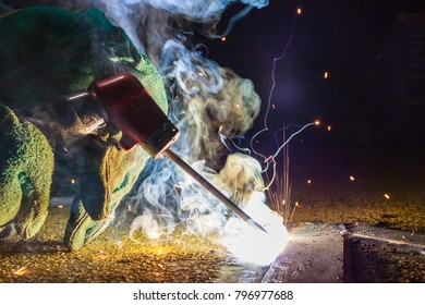 Industrial welder worker holding welding torch during perform welding sheet metal steel plate in construction factory by wearing heat protection gloves with smoke, spark, arc, fire, flash, hot
