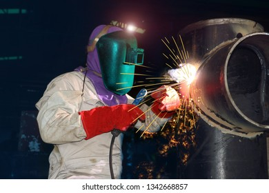 Industrial welding worker business concept with technician focus on welding process with equipment protective mask welder, leather gloves, PPE at construction site on Monochrome tone