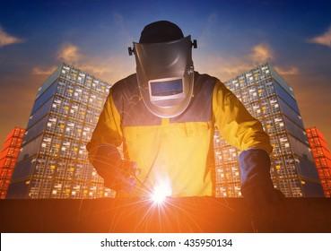 Industrial welding worker welding steel structure with cargo container stack in background.