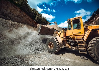 Industrial wheel loader working on construction site. Heavy duty machinery loading gravel and transporting materials