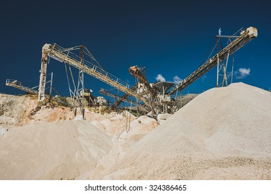 Industrial work processing of stones with a gravel sorter machinery reflected in water at a quarry with a clear blue sky