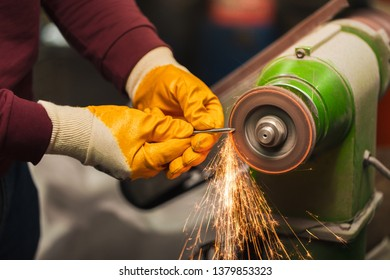 Industrial worker with angle grinder cutting metal with many sharp sparks on workplace. Worker with yellow gloves.