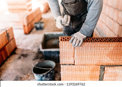 industrial worker, bricklayer and mason working with bricks and building interior walls of house