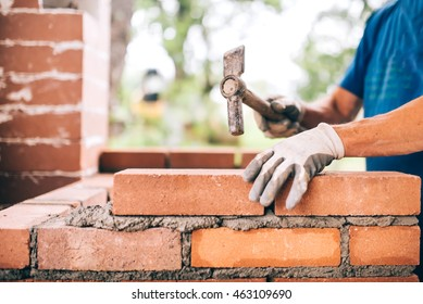 industrial worker building exterior walls, using hammer for laying bricks in cement. Detail of worker with tools