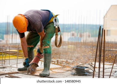 Industrial worker Cutting metal rebar at Construction site with an electric hand Grinder machine during tying steel bars for concrete reinforcement