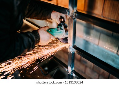 industrial worker cutting metal using angle grinder and throwing sparks