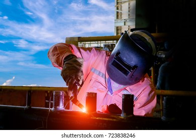 Industrial Worker at the factory tig welding on dark tone