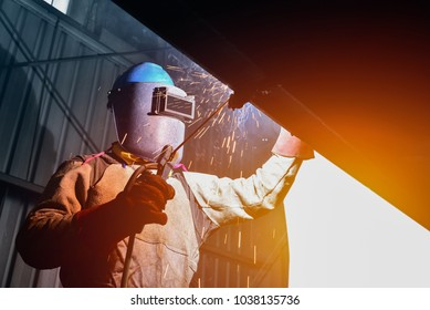industrial worker at factory welding close up by wear equipment and mask for protection on monochrome tone background