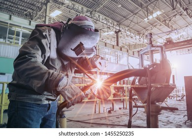 Industrial Worker at the factory welding process close up using Tig welder and spark light with protective equipment mask, PPE marks welder on Retro filter tone.