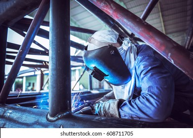 Industrial Worker at the factory welding, welding steel pipe structure
