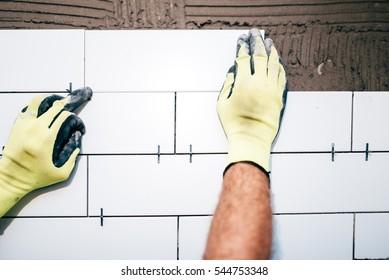 industrial worker hands installing ceramic tiles on interior walls, handyman using plastic distancer for adjusting tiles. Construction details