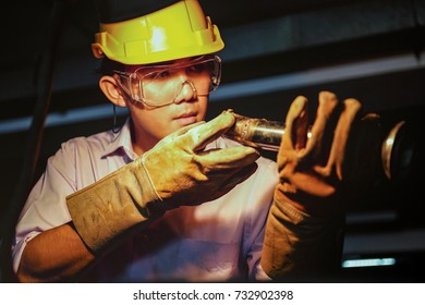 Industrial worker handsome man with protective workwear cutting metal in industry, equipment engineer safety with yellow hard helmet project of workman in the factory,