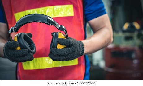 Industrial worker holding ear protection gear equipment.