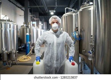 Industrial worker holding plastic cans with chemicals in production plant. Technologist wearing protection white uniform handling with aggressive chemicals substances.