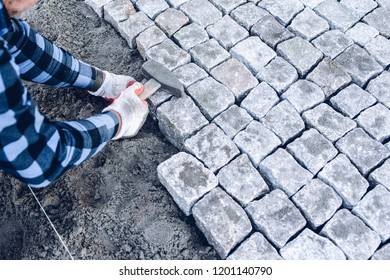 industrial worker installing pavement rocks, cobblestone blocks on road pavement