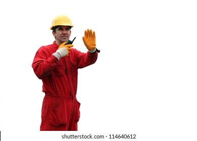 Industrial Worker - Isolated Over White Background. A portrait of a worker in red overalls and yellow helmet with talkie-walkie.
